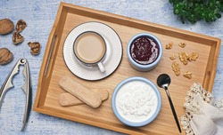 Healthy tasty breakfast. Cottage cheese, jam, coffee, cookies and nuts on a wooden tray. Flat lay, top view, rustic style.