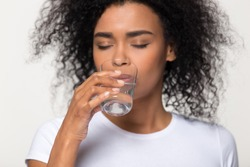Healthy thirsty african woman drinking clean mineral water isolated on white studio background, black lady feel dehydrated holding glass hydrating for body health beauty, hydration concept, close up