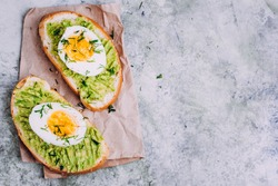 Healthy toast with avocado cream and egg on gray marble table background. Horizontal image, top view, copy space. Vegetarian food concept
