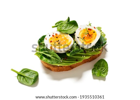 Healthy toast with sliced avocado, boiled eggs, spices and fresh spinach. Delicious breakfast or snack isolated on white background Stockfoto ©