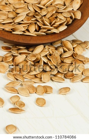 Healthy toasted pumpkin seeds spilling from a rustic wood bowl with focus on foreground seeds and copy space at bottom