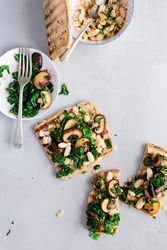 Healthy toasts for breakfast or lunch with whole wheat bread with cannelloni /kidney beans , sauteed mushroom and kale with garlic. Vegetarian sandwich. Plant-based diet. Whole food concept