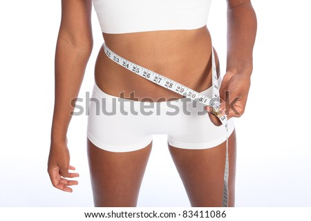 Healthy torso of young african american woman wearing white sports underwear, checking diet weight loss on waist with tape measure, standing against white background.