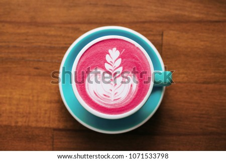 Healthy trendy beetroot latte with latte art in ceramic cup on wooden table. Top view.