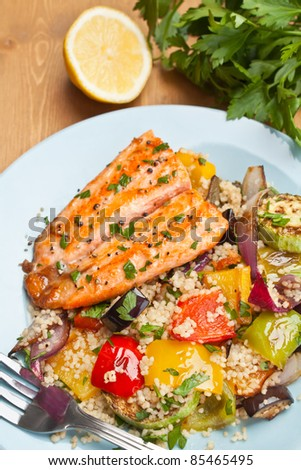 Healthy Trout with Roast Vegetables and Couscous Salad on a Wooden Table