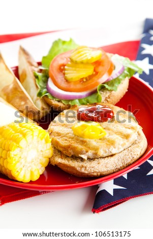 Healthy turkey burger on whole grain bun, with baked potato wedges and corn on the cob. Low fat picnic options photographed on the American Flag.