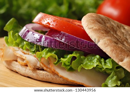 Healthy turkey sandwich on thin whole wheat deli roll with lettuce, onions and tomato on wooden cutting board with tomato and lettuce in background.  Macro with shallow dof.