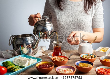 Healthy Turkish breakfast, with sliced tomato, cucumber, and white feta cheese, small bowls of strawberry jam, olive, honey, pepper paste. Tea is poured into traditional Turkish tea glass.  Stok fotoğraf ©