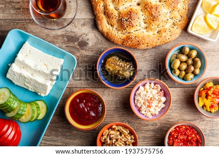 Healthy Turkish breakfast, with sliced tomato, cucumber, and white feta cheese, small bowls of strawberry jam, olive, honey, pepper paste. Tea is served in traditional Turkish tea glass. Ramadan feast Stok fotoğraf ©
