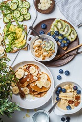 Healthy varied vegetarian breakfast table. Oatmeal with fruits, chia pudding, pancakes with banana and honey and toasts with fruits, vegetables and cream cheese, white background.