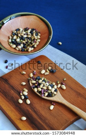 Healthy variety beans full in wooden spoon put on wooden board