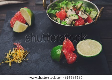Shutterstock Healthy vegan and vegetarian food on dark background. Citrus fruit slices and salad in copper bowl on black slate