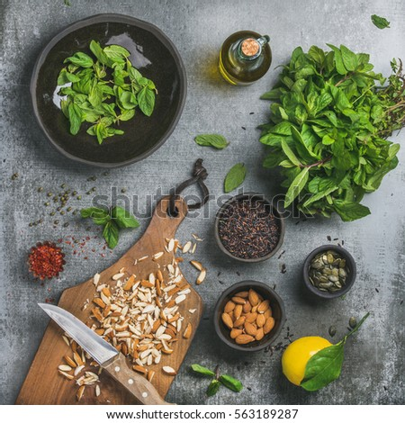 Healthy, vegan, clean eating cooking ingredients. Chopped almond, fresh mint, oil, black rice, pumpkin seed, spices, lemon over grey concrete background, top view, square crop Detox or dieting concept #563189287