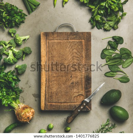 Healthy vegan ingredients layout. Flat-lay of green vegetables and herbs over concrete background with wooden board in center, top view, copy space, square crop. Vegetarian, clean eating concept