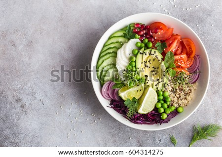 healthy vegan lunch bowl. Avocado, quinoa, tomato, cucumber, red cabbage, green peas and radish  vegetables salad. Top view