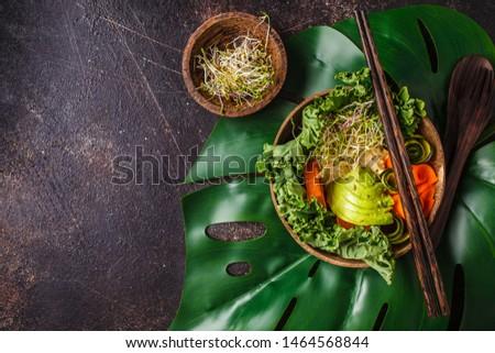 Healthy vegan lunch in a coconut bowl. Buddha bowl on a dark background. #1464568844