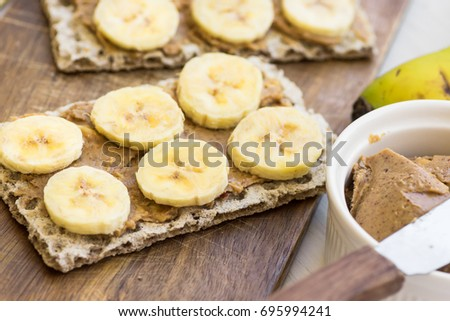 Healthy vegan snack with scandinavian rye crispbread, homemade peanut butter and slices of Canary island bananas