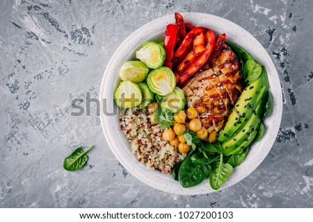 Healthy vegetable buddha bowl lunch with grilled chicken and quinoa, spinach, avocado, brussels sprouts, red paprika and chickpea on gray background. Top view.