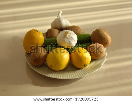 Healthy vegetables and fruits in a plate.lemon, kiwi, cucumber, garlic. Stok fotoğraf ©