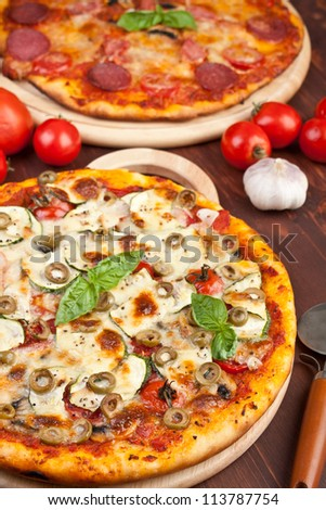 Healthy vegetables and mushrooms pizza and salami pizza at the back