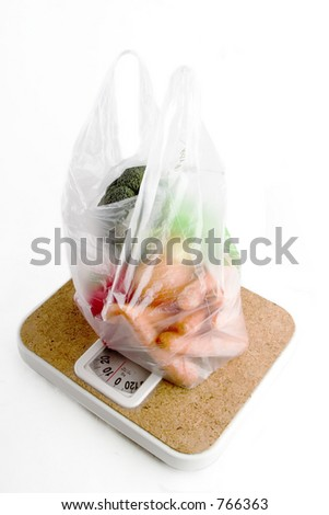 Healthy vegetables in a clear plastic grocery bag on a scale