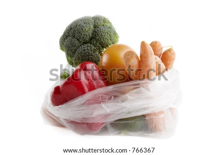 Healthy vegetables in a clear plastic grocery bag on a white background
