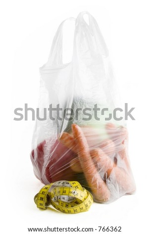 Healthy vegetables in a clear plastic grocery bag on a white background with a tape measure in the foreground
