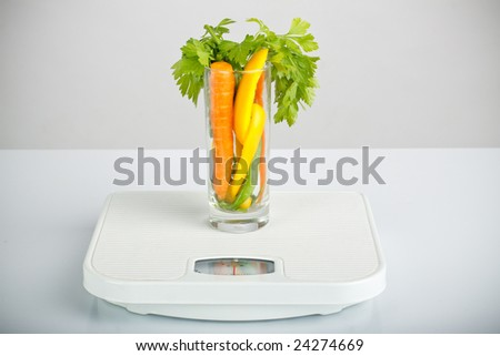 healthy vegetables in a glass on bathroom scales