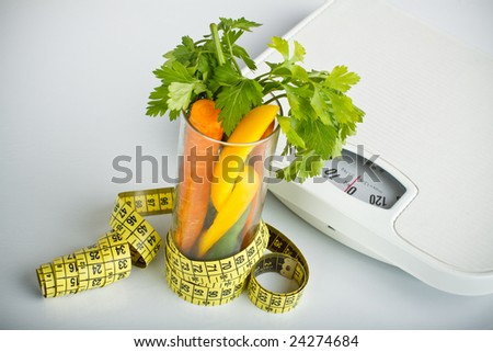 healthy vegetables in a glass surrounded by a measuring tape, bathroom scales in background