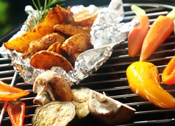 Healthy vegetarian barbecue with fresh vegetable grilling over the coals including bell pepper, carrots, potato and mushrooms