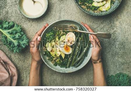 Healthy vegetarian breakfast bowls flat-lay. Quinoa, kale, green beans, avocado, egg with tahini dressing bowls over concrete background, top view. Energy boosting, clean eating, diet food concept