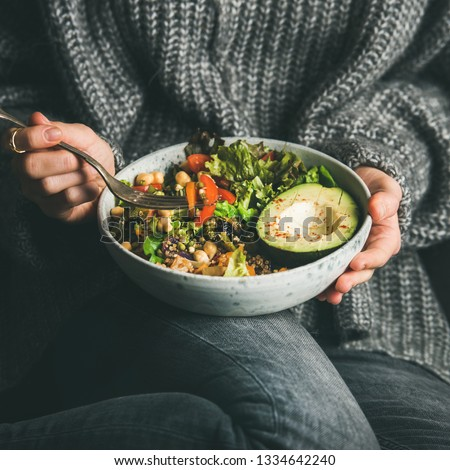 Healthy vegetarian dinner. Woman in grey jeans and sweater eating fresh salad, avocado, grains, beans, roasted vegetables from Buddha bowl, square crop. Superfood, clean eating, dieting food concept