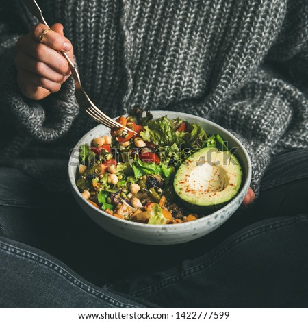 Healthy vegetarian dinner. Woman in jeans and sweater eating fresh salad, avocado half, grains, beans, roasted vegetables from Buddha bowl, square crop. Superfood, clean eating, dieting food concept