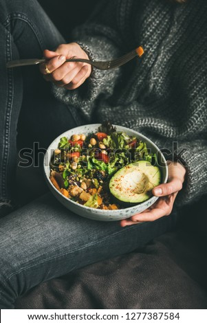 Healthy vegetarian dinner. Woman in jeans and warm sweater holding Buddha bowl with fresh salad, avocado half, grains, beans, roasted vegetables. Superfood, vegan, clean eating, dieting food concept
