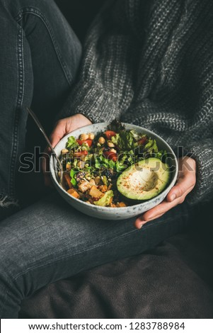 Healthy vegetarian dinner. Woman in jeans and warm sweater holding Buddha bowl with fresh salad, avocado half, grains, beans, roasted vegetables in hands. Superfood, clean eating, dieting food concept