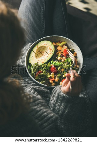 Healthy vegetarian dinner. Woman in jeans and woolen sweater holding bowl with fresh salad, avocado, grains, beans, roasted vegetables, top view. Superfood, clean eating, vegan, dieting food concept