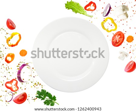 Healthy vegetarian eating and cooking with various flying chopped vegetables ingredients, plate isolated on white background. Concept diet and healthy eating.