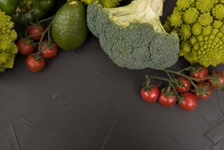Healthy vegetarian food, fresh green food, green vegetable, romanesco broccoli, pepper, zucchini and avocado, free space in your text, on a black table.