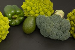 Healthy vegetarian food, fresh green food, green vegetable, romanesco broccoli, pepper, zucchini and avocado on a black table.