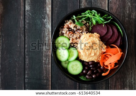 Healthy vegetarian nourishment bowl with hummus, beans, wild rice, beets, carrots, cucumbers and pea shoots. Above view on dark wood.