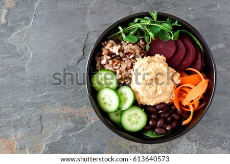Healthy vegetarian salad bowl with hummus, beans, wild rice, beets, carrots, cucumbers and pea shoots. Above view on slate background.