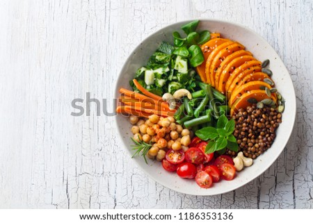 Healthy vegetarian salad. Buddha bowl. Wooden cracked background. Top view. Copy space.