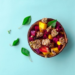 Healthy vegetarian sweet breakfast concept. Overhead still life of colorful smoothie with granola and tropical fruits in glass jar on pastel blue background.