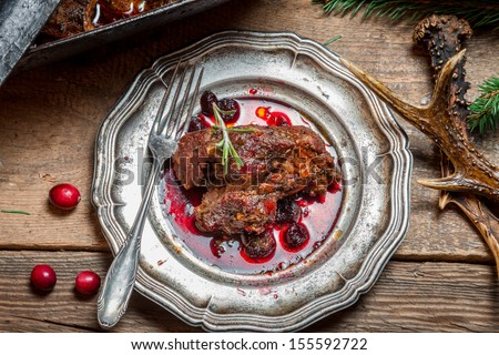 Healthy venison with cranberries and rosemary served on an old metal plate
