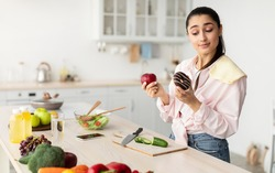 Healthy vs Unhealthy Food. Decisive doubtful woman holding red apple and donut in both hands, making choice of her meal, standing in kitchen, free copy space. Uncertain lady hesitating about her diet