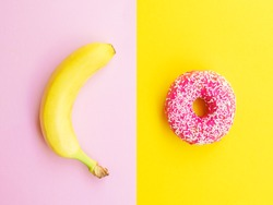 Healthy vs unhealthy food, dieting concept. Pink donuts, doughnut with sweet sprinkles on yellow and a banana isolated on pink color studio background with copy space. Flat lay, view from top.