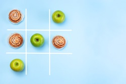 Healthy vs unhealthy food, green apples vs cinnamon buns in tic tac toe or noughts and crosses game, horizontal, top view,  copy space