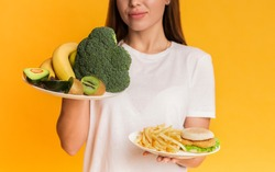 Healthy Vs Unhealthy. Unrecognizable girl choosing between plates with organic fruits and vegetables and junk food, yellow background, cropped