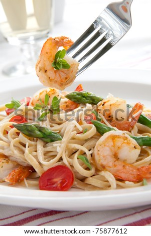 Healthy whole grain linguine with shrimps, asparagus, cherry tomatoes, fresh Parmesan cheese, and  oregano.