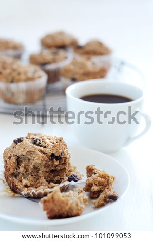 Healthy wholegrain bran muffin half eaten with a cup of coffee